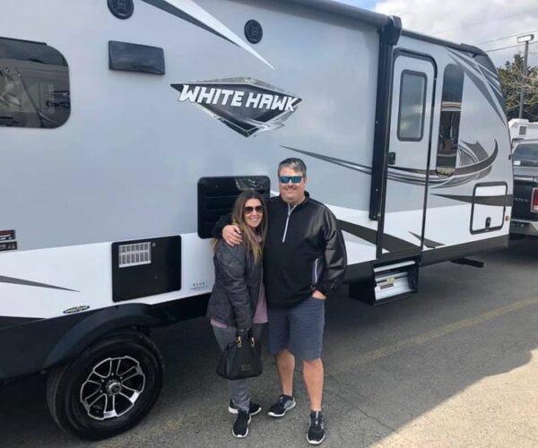 Happy couple standing next to RV