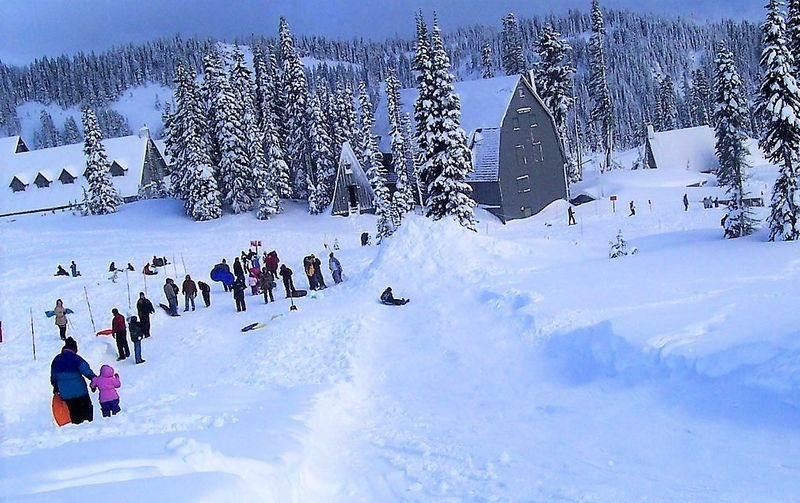 Families sledding on small mountain
