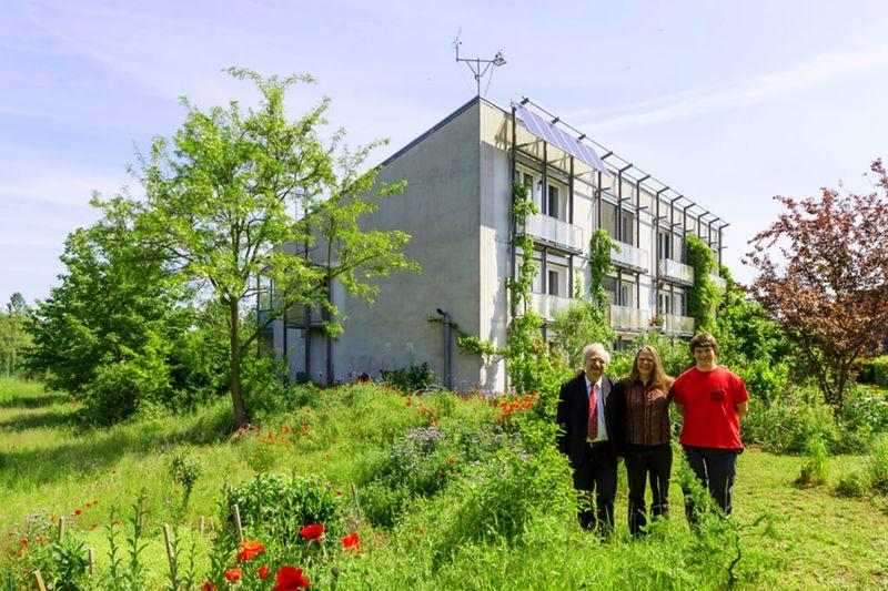 Three people next to passive solar house